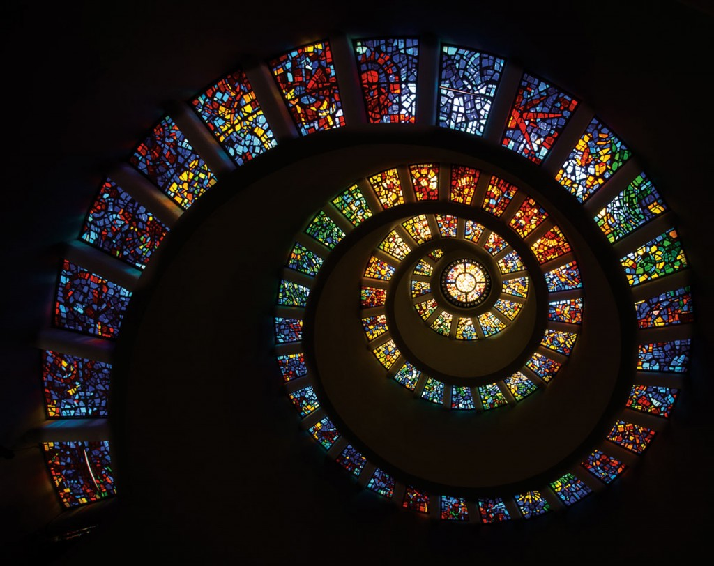 Full Spectrum Fibonacci by W Gary Rivera. The spiral of colored stained glass visually approximates a logarithmic spiral described in polar coordinates by r=a*e^(b*theta). The colors mimic those of the visual light spectrum from red to violet.